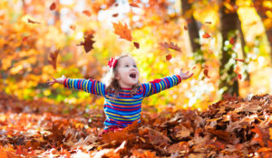 happy girl playing in fallen leaves